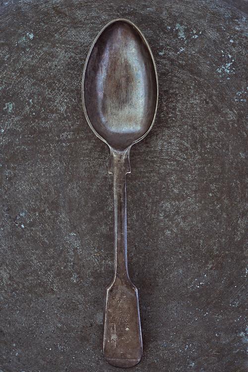 Antique tarnished silver teaspoon lying on tarnished metal