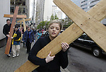 Jessica Delgado struggles with her cross as she and hundreds of others joined in on Good Friday's Stations of the Cross walking Meditation in downstown Seattle. Jim Bryant Photo