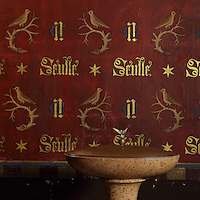 Font and wall painting with the motto of Nicolas Rolin, Seulle and a star, the initials N and G and a bird on a branch, in the Chapel, in the Salle des Povres or Room of the Poor, in Les Hospices de Beaune, or Hotel-Dieu de Beaune, a charitable almshouse and hospital for the poor, built 1443-57 by Flemish architect Jacques Wiscrer, and founded by Nicolas Rolin, chancellor of Burgundy, and his wife Guigone de Salins, in Beaune, Cote d'Or, Burgundy, France. The hospital was run by the nuns of the order of Les Soeurs Hospitalieres de Beaune, and remained a hospital until the 1970s. The building now houses the Musee de l'Histoire de la Medecine, or Museum of the History of Medicine, and is listed as a historic monument. Picture by Manuel Cohen