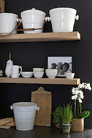The walls of the kitchen have been painted in a shade of ebony to highlight the collection of white faience ceramics displayed on the massive oak shelves