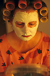Woman at dining room table with facial mask and hair in curlers looking into mirror