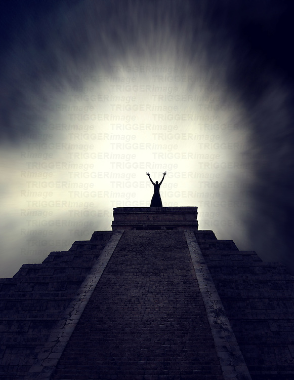 Man standing with arms raised on top of mysterious pyramid at night with glowing light