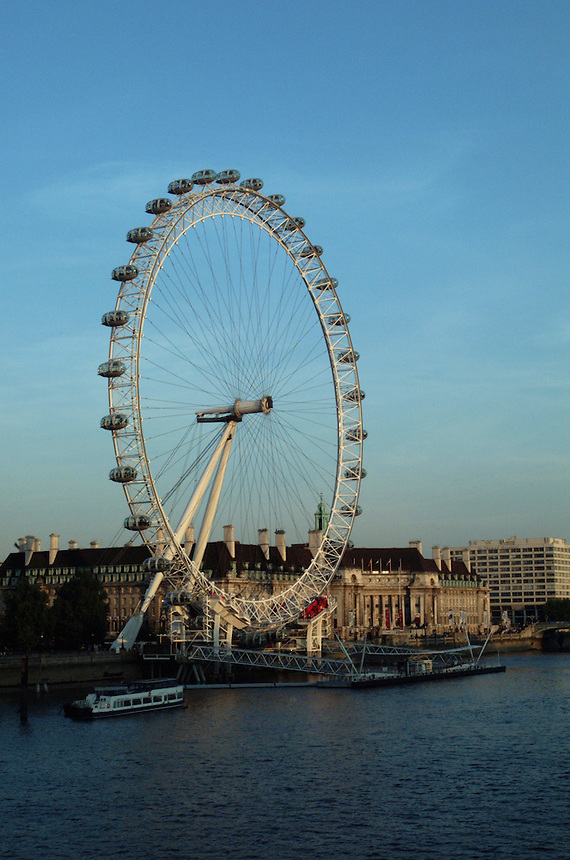 The London Eye (Millennium Wheel) seen from the opposite bank of the Thames, is a major tour attraction in London, England, shown here in 2006.