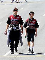 Jul. 20, 2014; Morrison, CO, USA; NHRA top fuel driver Larry Dixon (left) walking with his son Donovan Dixon during the Mile High Nationals at Bandimere Speedway. Mandatory Credit: Mark J. Rebilas-
