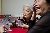 Former farmers play cards in southern China in her newly furnished apartment given by the government in return for seized land.<br /> <br /> China is pushing ahead with a dramatic, history-making plan to move 100 million rural residents into towns and cities over six years &mdash; but without a clear idea of how to pay for the gargantuan undertaking or whether the farmers involved want to move.<br />