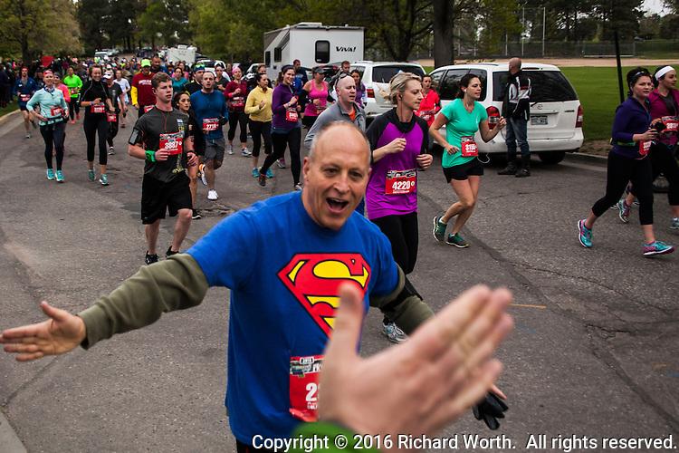 Unidentified half-marathoner shares a high-five with a sideline cheerleader at the 2016 Colfax Marathon in Denver, Colorado.