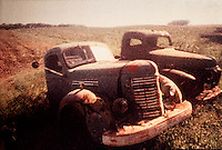 Polaroid transfer, two abandoned rusting trucks in field.