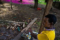 A young Somali immigrant, heading to the southern U.S. border, fills a bottle with drinking water in a military base in the jungle of Darién gap in Panama, 29 January 2015.