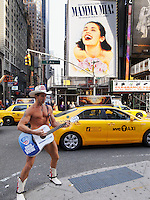 USA. New York City. The naked cowboy and his guitar is performing live on Times Square. Yellow cabs and billboards for the musical show Mamma Mia on Broadway Avenue. 26.10.2011 © 2011 Didier Ruef