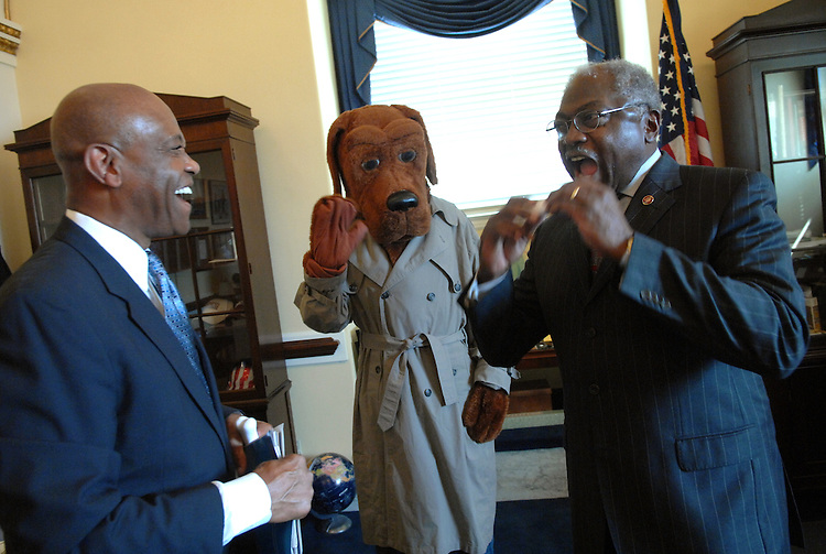 House Majority Whip James Clyburn, D-S.C., bites into a toy bone, a gift from McGruff the Crime Dog, and Alfonso Lenhardt, president and CEO of the National Crime Prevention Council, during a trip to the Whip's office.  The month of July is McGruff's 27th birthday and was making rounds on the Hill to draw attention to crime prevention.