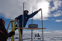 Scientists using ice-based weather stations and instrument towers to record air temperature, wind speed and direction, and levels of solar radiation on the Greenland ice sheet.