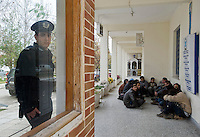 Early morning in the border town of Orestiada. A security guard stands by as Afghan refugees rest after crossing the boder from Turkey into Greece. They are reporting themselves in to the local authorities at the police station. According to UNHCR, 38,992 immigrants arrived in Greece in the first 10 months of 2010, whereas in 2009 the number was only 7,574.