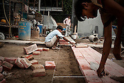 Construction workers are seen working on the pavement of the Jawahar Lal Nehru stadium in New Delhi, India.