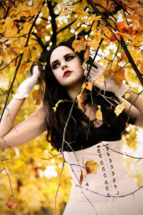 A girl with pale skin and long black hair, wearing a white corset dress and gloves standing among autumnal trees and looking away.