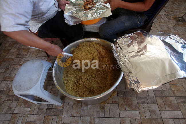 Palestinians prepare rice as they wait for customers several hours before Iftar, the breaking of the day long Ramadan fast in Gaza City, on Aug. 04, 2012. Muslims around the world refrain from eating, drinking and sexual intercourse from dawn till dusk during Ramadan, the holiest month in the Islamic calendar. Photo by Ashraf Amra