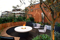Wide angle view of tiny roof terrace with burning flambe' arching wooden bench and olive tree in foreground