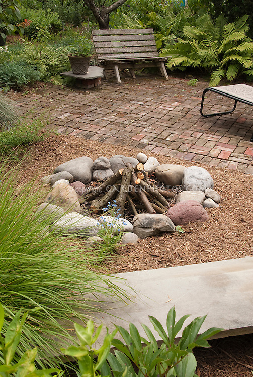 Cooking Fire in Backyard with brick patio, fireplace made of stones, with bench and plants