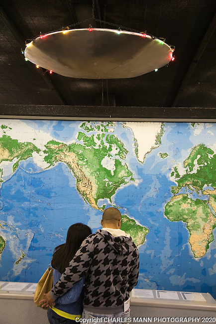 A UFO light fixture hoovers over a young couple and a map of the world at the UFO Museum in Roswell, New Mexico