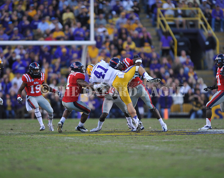 LSU's Dickson (41) is tackled by Ole Miss defensive back Trae Elston (7) and Ole Miss linebacker Mike Marry (52) at Tiger Stadium in Baton Rouge, La. on Saturday, November 17, 2012. LSU won 41-35.....