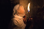 An Orthodox-Ethiopian Christian pilgrim at Deir Al-Sultan, the Ethiopian section of the Church of Holy Sepulchre in Jerusalem's old city, during the Holy Fire ceremony as part of Easter. The ancient fire ritual celebrates the Messiah's resurrection after being crucified on the cross.