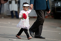 A Bangladeshi child walking with her father as they along with others stand in a queue to pay homage at the Dhaka Central Shaheed Minar, or Martyr's Monuments on International Mother Language Day in Dhaka, Bangladesh, Saterday, Feb. 21, 2015.