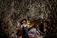 "Ventura, California, July 23, 2010 - A portrait of Tim 'Timbow' Bowman in front of his tent that is hidden by the 16-foot tall grass and bamboo on the Ventura River bottom. Bowman has been homeless and living along the river since the early 1990's.  In 1987 his 18-month-old daughter, Miranda Laurel, died from Lyme disease. His wife left him soon afterwards. A year later he fell through a plate glass window while working on a construction site, leaving him disabled and unable to work construction. He says the loss of his wife and daughter and his struggles with work sent him into a spiral. He eventually lost his home. He says he lives in the 300+ community along the river bottom because he ""feels at home."" Adding, ""I feel loved down here. Up there is nothing but trouble."" The two-mile stretch of river bottom from the Pacific to Stanley Road is home to about 300 homeless, who have carved tunnels and paths into the tall grass and bamboo. Bowman, who survives off of SSI, says, ""I lead an honest life. I don't steal, I don't rob and I share whatever I can."" ."