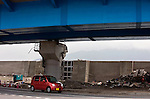A car drives under an overpass where a boat  had previously been wrapped around the supporting pillar following the March 11 tsunami that swept it there in Miyako, Iwate Prefecture, Japan on  11 June 20011, 3 months after the disaster took place.  .Photographer: Robert Gilhooly