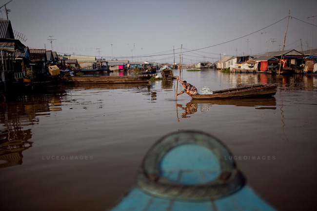 "A boy paddles through the river neigborhood on the Hau Giang River, a tributary of the Mekong River, in Chau Doc, in the An Giang Province, Vietnam. When the Mekong River reaches Vietnam it splits into two smaller riveres. The ""Tien Giang"", which means ""upper river"" and the ""Hau Giang"", which means ""lower river"". Photo taken on Monday, December 7, 2009. Kevin German / Luceo Images"