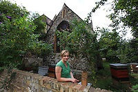 Camilla Goddart, 38 years old, posing in front of her first hive in the garden of St Peters Church in Brocley where she started 8 years ago. Since, this graphic designer by training created a company, &quot;Capital Bee&quot;, that sells honey in the markets or in shops and caf&Egrave;s like Broca Market, Brockley, The Frog on the Green Deli in Nunhead, Cafe Crema in New Cross and El's Kitchen in Ladywell. ? ????<br /> &acute; I go through various obsessions, when I was young it was growing tropical fruit, when I was at Cambridge it was English Literature, then art, then japanese woodcuts, then extraordinary victorian copper jellymoulds for puddings at banquets, then herbs and their uses, then decorative vegetable gardens and making potagers, then antique african masks, though in the end keeping bees has proved to be the most enduring as they are so complex and are teaching me all the time about their mysterious world.  I even look after nests of bumblebees now in wooden boxes in the apiary they are terrific characters, people get them mixed up with bees and sometimes want them removed, though it is always best to leave them alone ideally as they rarely do any harm!???? &ordf;