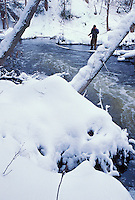 A MAN SCANS THE WATERS OF THE CARP RIVER NEAR MARQUETTE MICHIGAN WHILE FLY FISHING FOR STEELHEAD FOLLOWING A SNOW STORM.