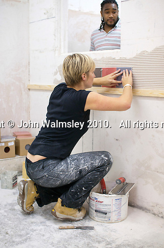 Student doing a course in tiling applying the tiles.  Able Skills in Dartford, Kent, runs courses in construction industry skills like, bricklaying, carpentry and tiling.