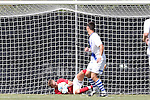 31 August 2014: Stetson's Paul Ladwig (in red) makes a save on Duke's Brody Huitema (CAN) (in white). The Duke University Blue Devils hosted the Stetson University Hatters at Koskinen Stadium in Durham, North Carolina in a 2014 NCAA Division I Men's Soccer match. Duke won the game 8-2.