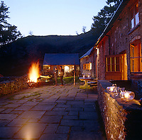 A couple admiring the blaze from a brazier on the paved terrace of the cottage as night falls