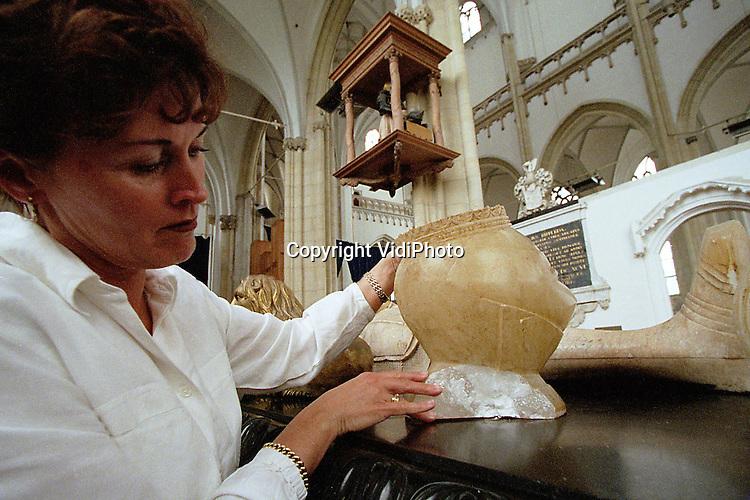 Foto: VidiPhoto..ARNHEM - Een mederwerkster van de Eusebiuskerk in Arnhem toont de schade aan de graftombe van de hertog van Gelre. Een verstandelijk gestoorde bezoeker heeft zondag de 30 kilo zware albasten helm tegen het kostbare monument kapotgegooid. Nog deze week komt Monumentenzorg de schade opnemen. Van de helm en het monument zelf zijn stukken afgebroken. .De schade wordt vooralsnog geschat op rond de honderdduizend gulden. De verdachte, die al eerder voor problemen zorgde in de kerk, is inmiddels .opgenomen in een psychiatrische inrichting.