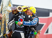 Sep 18, 2016; Concord, NC, USA; NHRA funny car driver John Force (right) gives top fuel winner Antron Brown a kiss as he celebrates after winning the Carolina Nationals at zMax Dragway. Mandatory Credit: Mark J. Rebilas-USA TODAY Sports