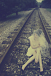 A woman in a white dress with her face veiled by white tulle sits and smokes sadly on some train tracks.