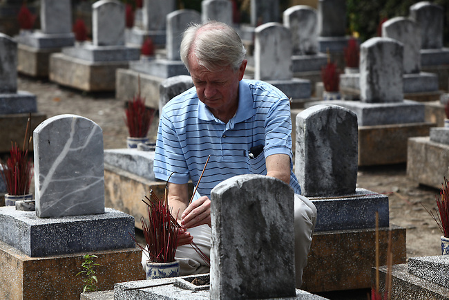 Chuck Searcy, of Veterans for Peace and Project RENEW, places a burning incense stick on the grave of a Vietnamese soldier at Truong Son Martyrs Cemetery in Quang Tri province, Vietnam. The cemetery contains the graves of about 10,300 communist soldiers who died along the Ho Chi Minh Trail supply network into South Vietnam during the conflict from 1959 to 1975. April 24, 2013.