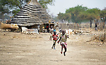 Children run in Leu, a village in the contested Abyei region along the border between Sudan and South Sudan. The village was looted and burned in 2011 when soldiers and militias from the northern Republic of Sudan swept through the area, chasing out more than 100,000 Dinka Ngok residents. A few thousand families have returned since northern combatants withdrew in 2012, yet their life is precarious. In Leu, the Catholic Church rehabilitated a clinic and drilled a well. For political and logistical reasons, the Catholic Church is one of the few organizations willing to openly accompany the people of Abyei during these uncertain times.