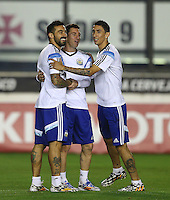 Ezequiel Lavezzi, Lionel Messi and Angel Di Maria of Argentina hug each other during the training session