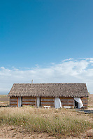 White curtains blow in the gentle breeze across the doors of this thatched cabin at CasasNaAreia