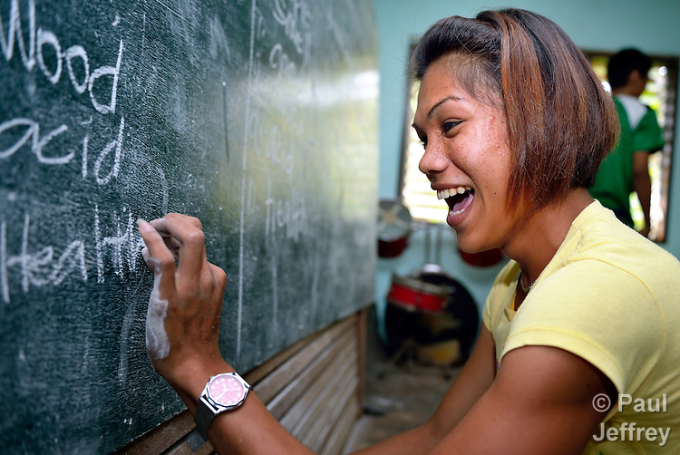 A woman writes joyfully on the blackboard as she participates in an adult literacy class in the village of Magsaysay, in New Bataan in the Compostela Valley on Mindanao Island in the southern Philippines.