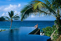 A girl sits on the rim of the horizon pool overlooking the Indian Ocean