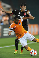Washington D.C. - May 17, 2014: Corey Ashe (26) of Houston Dynamo gets fouled by Fabian Espindola (9) of D.C. United. D.C. United defeated  the Houston Dynamo 2-0 during a Major League Soccer match for the 2014 season at RFK Stadium.