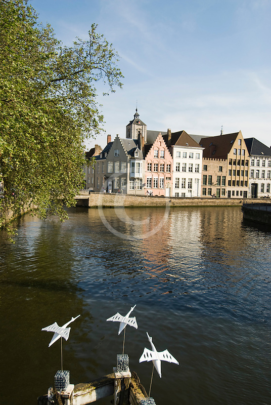 Belgium, Bruges, Canal and sculpture of white birds