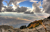 View from Sandia Crest (10,678 ft) of Albuquerque NM when a storm was rolling in. The snow was just beginning, creating water drops on the rocks, HDR image