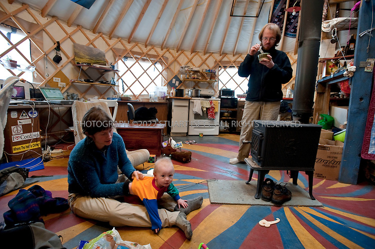 12/11/2009--Seldovia, Alaska, USA..Erin McKittrick changes her son, Katmai's daiper in their yurt in Seldovia, Alaska...The yurt is made by Nomad Shelter in Homer, Alaska, and cost about $14,000. Bretwood Higman ('Hig'), 33 and Erin McKittrick, 30, built it in November, 2008 on land owned by Hig's mother in Seldovia.The yurt is 24' in diameter, the ceiling is over 12' in the middle, 7' around the edge. It has no running water but does have electricity and internet access...McKittrick grew up in Seattle and met Higman, from Seldovia, at Carleton College in 2001. In June 2007, the couple left Seattle for the Aleutian Islands, traveling 4000 miles solely by human power through some of the most rugged terrain in the world; their adventure has recently been published in a book written by McKittrick with Hig's photographs titled, 'A Long Trek Home: 4,000 Miles by Boot, Raft, and Ski'...Together, the couple also run a small environmental non-profit, Ground Truth Trekking, which uses trekking to explore the complexities of natural resource issues. The couple lives with their 10 month old son son, Katmai, in Seldovia, Alaska, a 300 person village just off the end of the road system...©2009 Stuart Isett. All rights reserved.