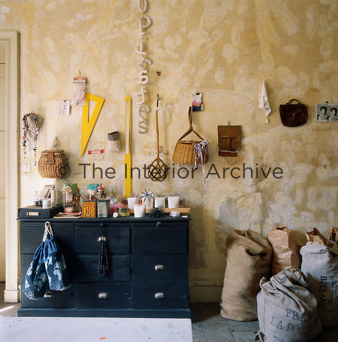 A collection of sacks and paper bags makes a rustic arrangement standing against the wall, which has a distressed finish.