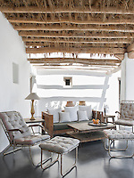 A comfortable outdoor seating area under the covered terrace furnished with rustic deck chairs and footstools upholstered in neutral linen
