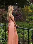 Young beautiful woman in a long dress standing on a bridge in a park. Springtime scenic.