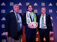 #21 overall pick Jimmy Ockford of the Seattle Sounders stands with head coach Sigi Schmid (left) during the MLS SuperDraft at the Pennsylvania Convention Center in Philadelphia, PA, on January 16, 2014.